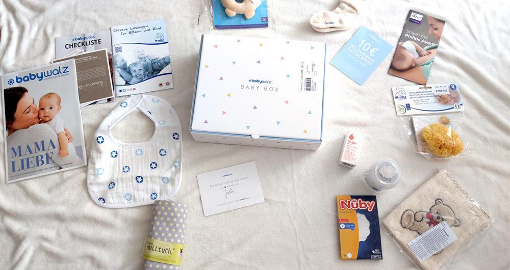 Die Babybwalz Babybox vom Juni 2018 liegt in der Mitte einer weißen Decke. Herum ist der Inhalt verteilt